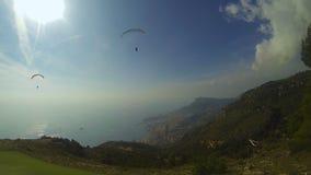 Paragliders que voam sobre os montes no dia ensolarado, cidade de beira-mar no pé, esportes extremos video estoque