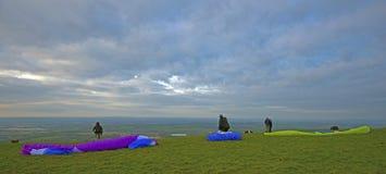 Paragliders que wainting para o vento no monte do cavalo branco de Westbury em Wiltshire, Inglaterra do sul imagem de stock