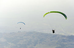 Paragliders silhouette flying over misty mountain Royalty Free Stock Photography