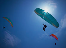 Paragliders soaring in a blue sky Stock Photo