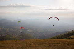 Paragliders. Some colorful paragliders flying over a mountain scenery, with some faint sunrays royalty free stock image