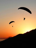 Paragliders in sunset coastal landscape. Two silhouette paragliders outdoors, flying in sunset sky, coastal landscape Royalty Free Stock Images