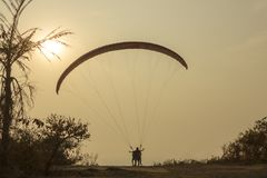 Paragliders tandemowy zdejmować od falezy przeciw tłu susi drzewka palmowe, trawa i jaskrawy słońce w wieczór zmierzchu niebie, zdjęcie royalty free