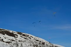 Paragliders on vibrant blue sky over snowy mountain Stock Photography