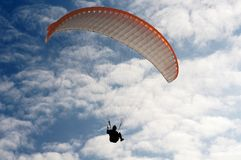 Paragliding. Para glider (white & orange) in mid air, background blue sky and clouds, photographed from below royalty free stock images