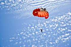 Paragliding. Red and orange on sky blue Stock Images