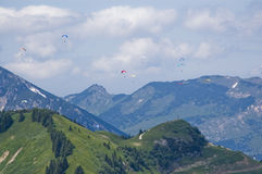 Paragliding. Numerous paragliders over a mountain landscape Stock Photos