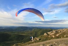 Paragliding. Paraglider lifting from a Norwegian mountain Stock Image