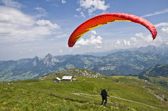 Paragliding. Man taking off with a paraglide from the top of a mountain: one of the favorite extreme sports in Switzerland Royalty Free Stock Image