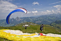 Paragliding. Men taking off with a paraglide from the top of a mountain: one of the favorite extreme sports in Switzerland Royalty Free Stock Image