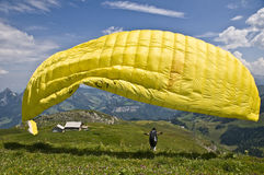 Paragliding. Man taking off with a paraglide from the top of a mountain: one of the favorite extreme sports in Switzerland Stock Images