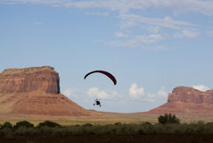 Paragliding. A powered paraglider pilot in flight over Monument Valley Stock Image