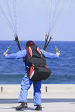 Paragliding. Man landing on ground near the sea Stock Image