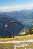 Paragliding above mountain lake Stock Photo