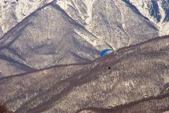 Paragliding above mountains. Person gliding in a parasail above mountains Stock Photography