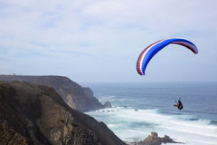 Paragliding above the ocean at Castelejo beach in Portugal Royalty Free Stock Image