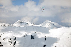 Paragliding above snow covered mountains Royalty Free Stock Photos