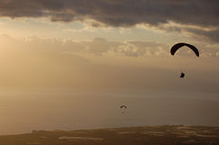 Paragliding backlit flying over coast and sea Tenerife Royalty Free Stock Images