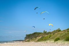 Paragliding in the beach stock images