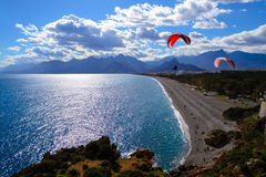 Paragliding by the beach and the mountains Royalty Free Stock Photo