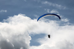 Paragliding in the blue cloudy skies Royalty Free Stock Photo