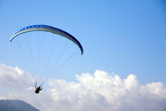 Paragliding in blue sky. Over a mountains Royalty Free Stock Photo