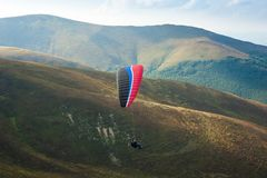 Paraglider fly over a mountain valley on a sunny summer day. royalty free stock photo