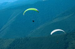 Two paragliders fly over a mountain valley on a sunny summer day. Royalty Free Stock Photography