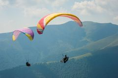 Two paragliders fly over a mountain valley on a sunny summer day. Stock Photography