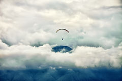 Paragliding among clouds above mountain range Royalty Free Stock Photo