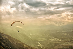 Paragliding among clouds above mountain range Stock Photo