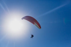 Paragliding in Crimea. Paragliding in the blue sky at sun disk background Stock Photo