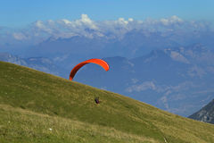 Paragliding in the Dolomites (Italy). View of the paraglider above the meadow. Dolomites mountains in the background Stock Images