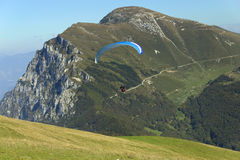 Paragliding in the Dolomites (Italy). Paraglider, which started to fly with a blue parachute in the alpine environment. (Dolomites, Italy Royalty Free Stock Photography