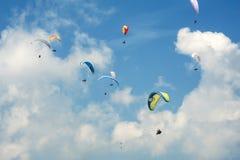 Paragliding en el cielo soleado azul El grupo de alas flexibles vuela en día soleado del verano en los Cárpatos Fotos de archivo libres de regalías