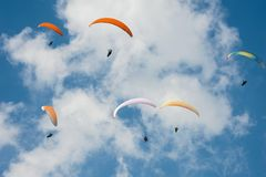 Paragliding en el cielo soleado azul El grupo de alas flexibles vuela en día soleado del verano en los Cárpatos Fotos de archivo