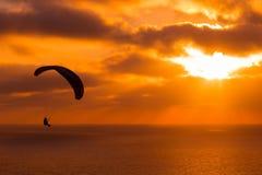 Paragliding en la puesta del sol con sorprender el cielo nublado y el sol que brillan a través de las nubes foto de archivo