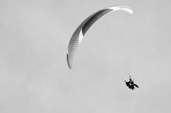 Paragliding en montañas en tiempo de primavera Espacio en blanco para un texto Cuadro blanco y negro Hombres en el lado derecho Foto de archivo