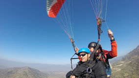 Paragliding, extreme sport. Tourist playing paragliding guided by a pilot Stock Photography