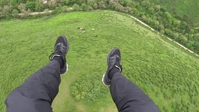 Paragliding. First person view. I look at sneakers, legs, pants, green hills. Paragliding. First person view. I look at sneakers, legs, pants, green hills stock footage