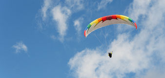 Paragliding flight with blue sky. And some clouds royalty free stock photo
