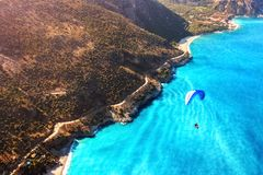 Paragliding flight over the sea coast of the Mediterranean Sea. Blue parachute against the blue sea. Turkey. Oludeniz. Aerial phot Royalty Free Stock Photo
