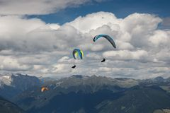 Paragliding flying through the Alps. Paraglider flying over the Alps from Kronplatz peak Royalty Free Stock Image