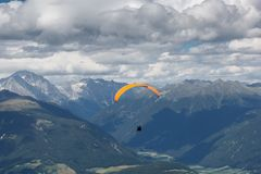 Paragliding flying through the Alps. Paraglider flying over the Alps from Kronplatz peak Royalty Free Stock Photography