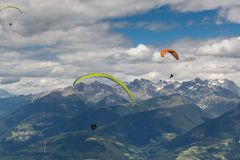 Paragliding flying through the Alps. Paraglider flying over the Alps from Kronplatz peak Stock Image