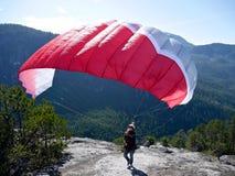 paragliding Frau mit einem roten Gleitschirm auf die Oberseite des Berges Stockfotografie