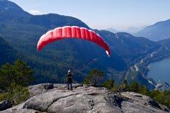 paragliding Frau mit einem roten Gleitschirm auf die Oberseite des Berges Lizenzfreie Stockfotografie