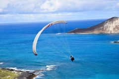 Paragliding in Hawaii. A men is paragliding in the blue sky of hawaii, in between two islands Royalty Free Stock Photography