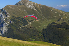 Paragliding in the high mountains. (Italy). Paraglider, which started to fly with a red parachute in the alpine environment. (Dolomites, Italy Royalty Free Stock Photos