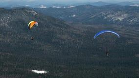 Paragliding i vinter mot bakgrunden av snö-korkade berg som täckas med skogen stock video